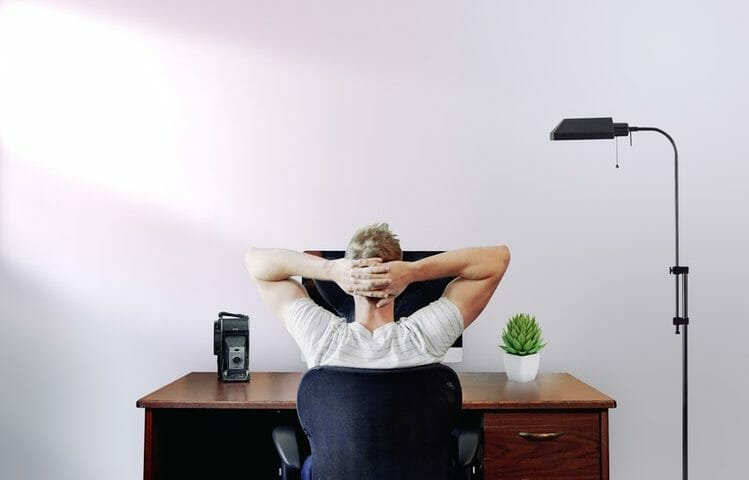 Man sitting in front of a computed with his hands crossed behing his neck